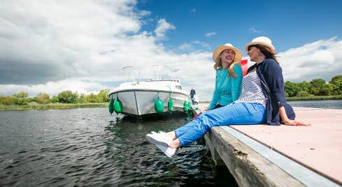 Two people wearing hats relaxing beside a river and boat in  Portumna, Co. Galway in Ireland's Hidden Heartlands.
