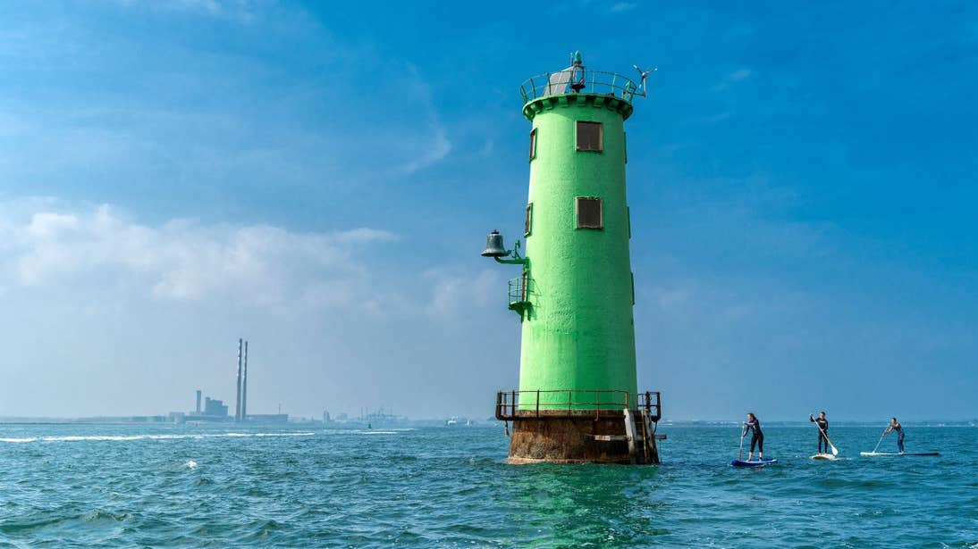 People stand-up paddleboarding beside North Bull Lighthouse on Dublin Bay