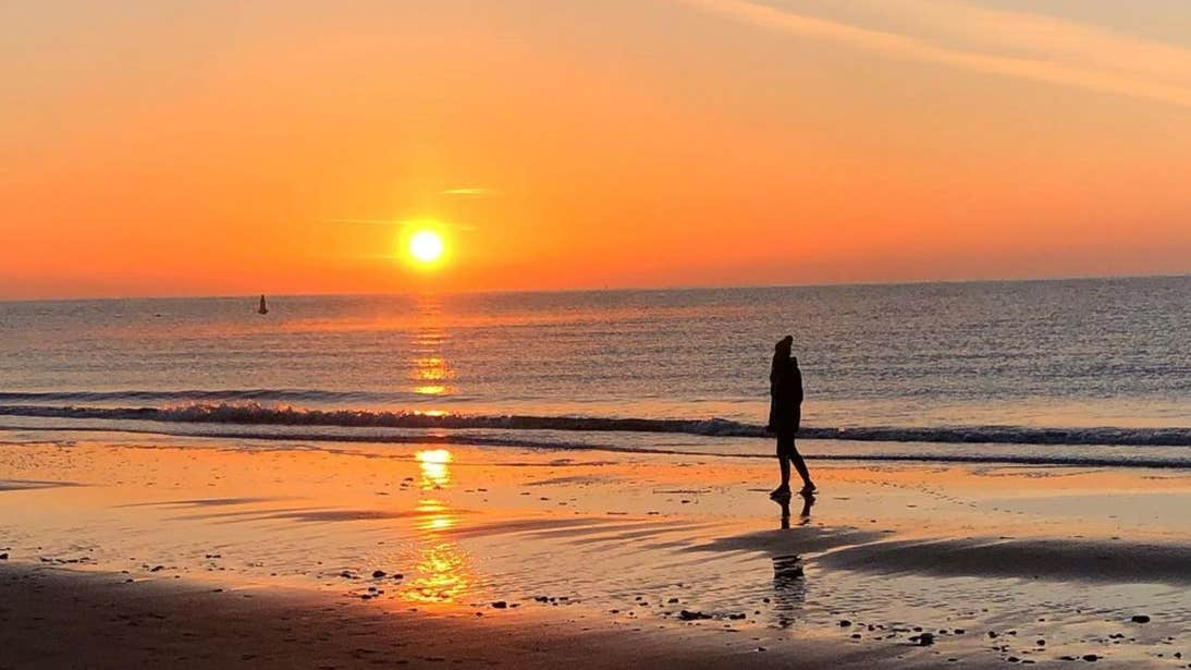 A person walking down Morriscastle Beach, County Wexford at sunset.