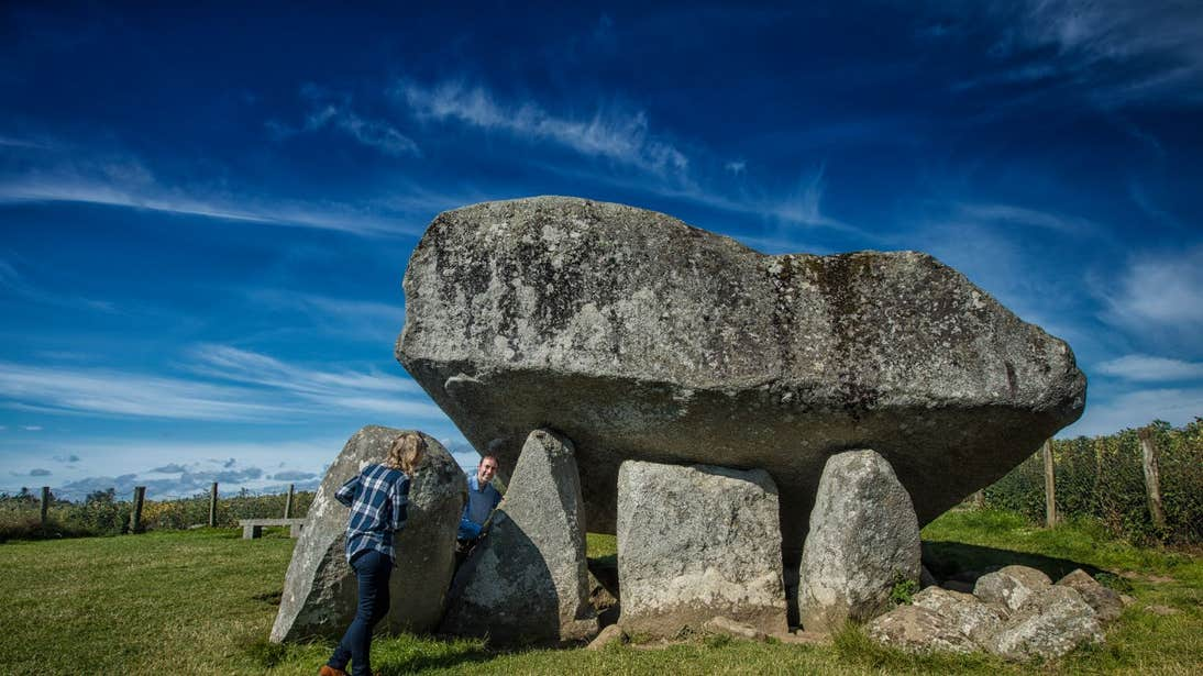 Two people exploring Brownshill Dolmen In County Carlow