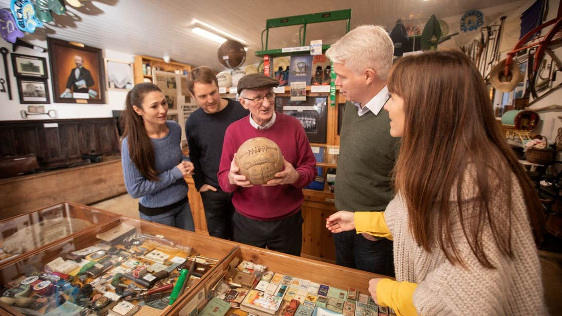 Man showing people an old football in Derryglad Folk Heritage Museum in Roscommon