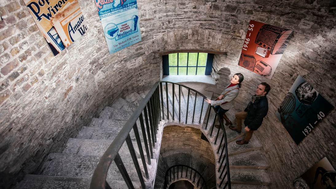 Two people walking up a winding stone staircase in Cork City Gaol