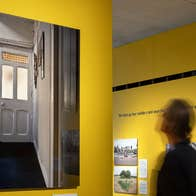 A man viewing photo art hung on a yellow wall and four other images are hanging on a wall behind him