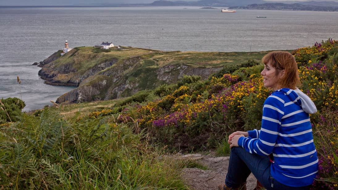 A woman sitting down looking out at the stunning views of Howth Head.