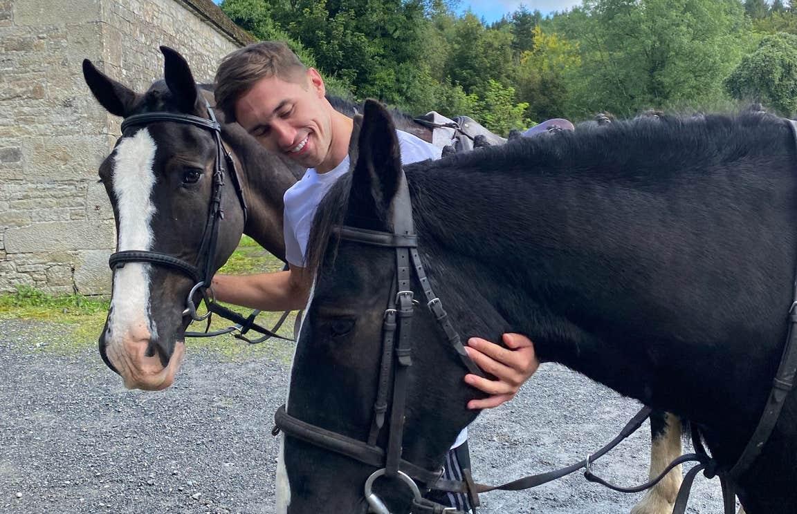 Greg O'Shea petting two horses at Birr Equestrian Centre
