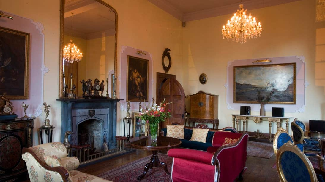 A chandelier, fireplace and furniture in the grand interior of Kinnitty Castle