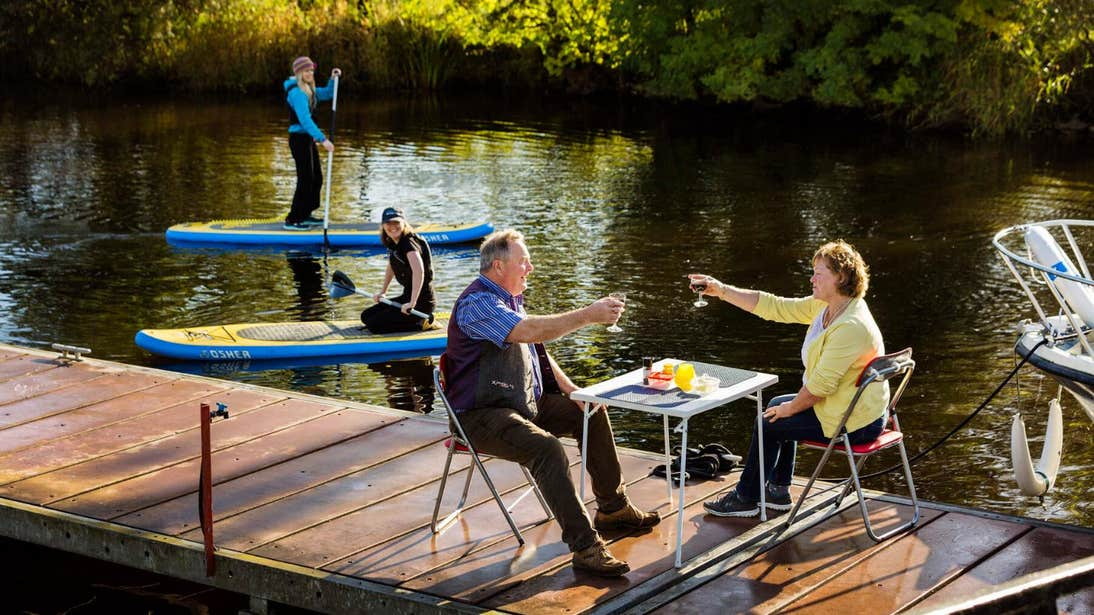 A couple having a meal beside a waterway in Leitrim with two people on stand-up paddleboards in the background