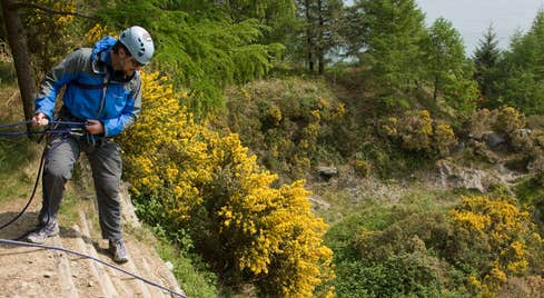 Man in a blue jacket starting to abseil down a rockface, Carlingford County louth