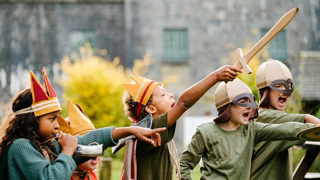 Young kids in costume playing games with swords and helmets
