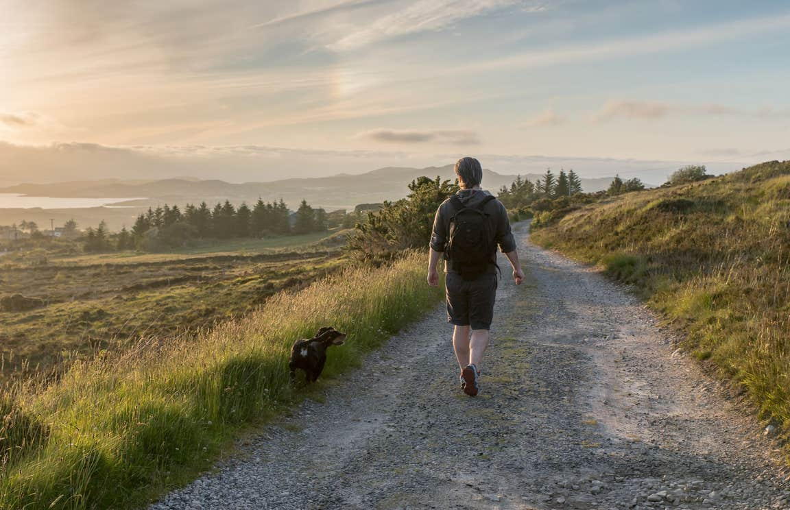 A man and his dog walking in Co. Donegal with views of trees and mountains in the distance