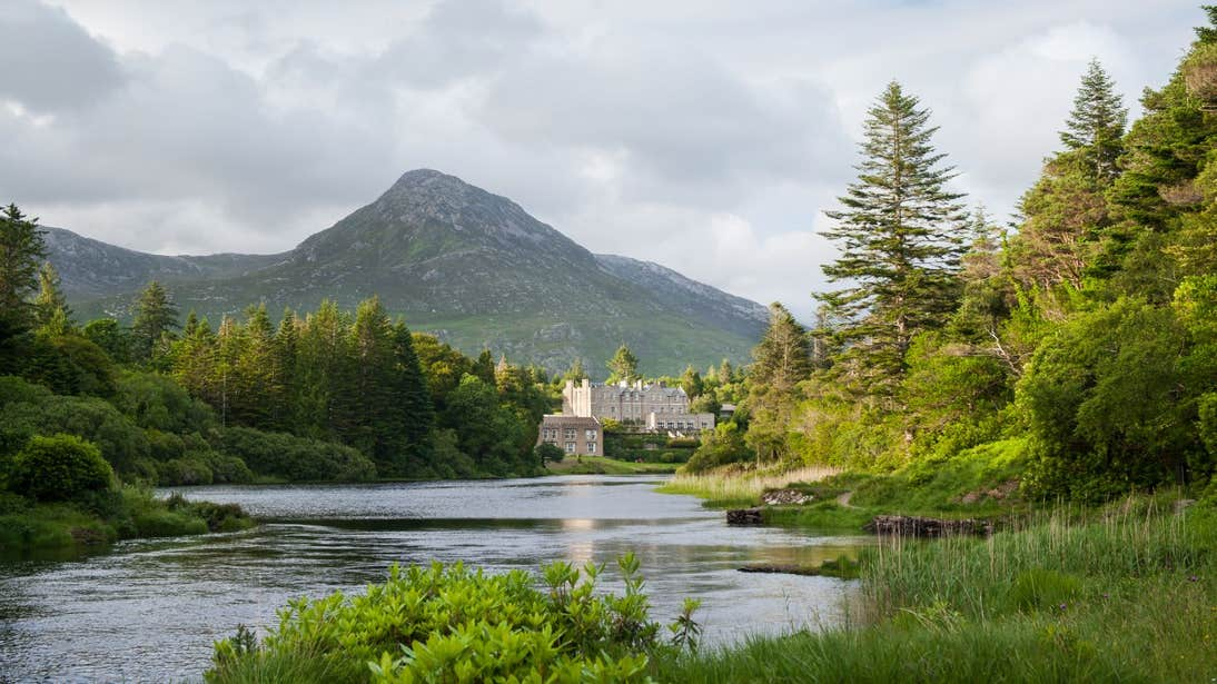 A castle reflected in a lake with a backdrop of mountains in Connemara, Galway