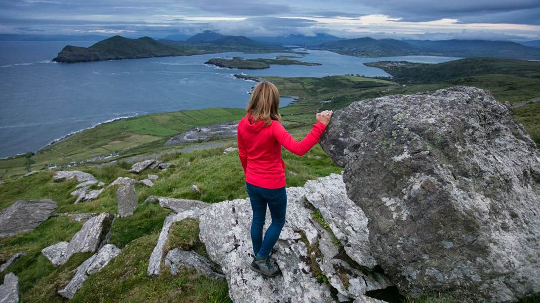 A woman in a red jacket hiking by the sea on Valentia Island, Co Kerry
