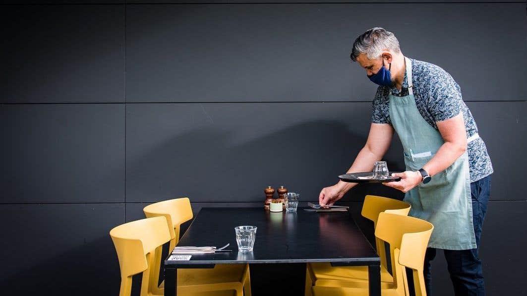 Waiter setting the table at Good Day Deli, Nano Nagle Place, Cork City