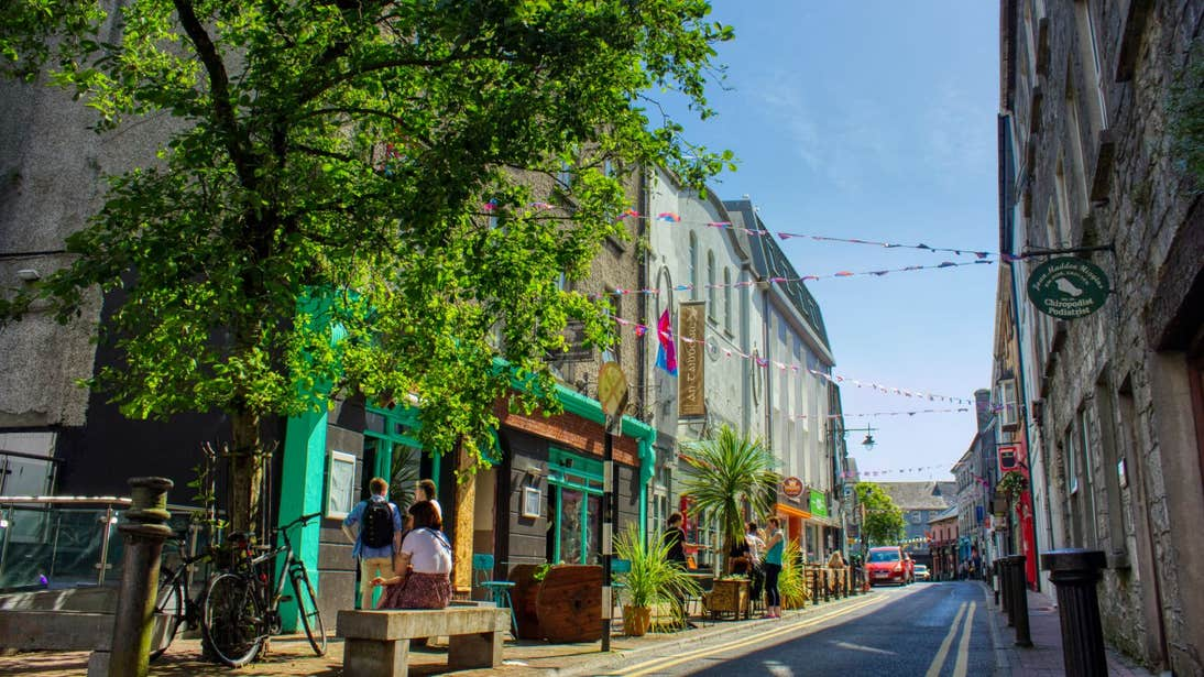 A street with brightly painted buildings, greenery and bunting in Galway City, Galway
