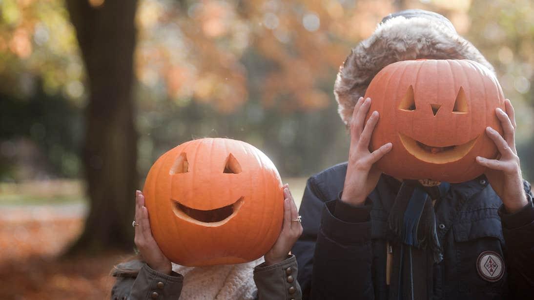 Two kids playing with Jack-o-lanterns at Halloween.
