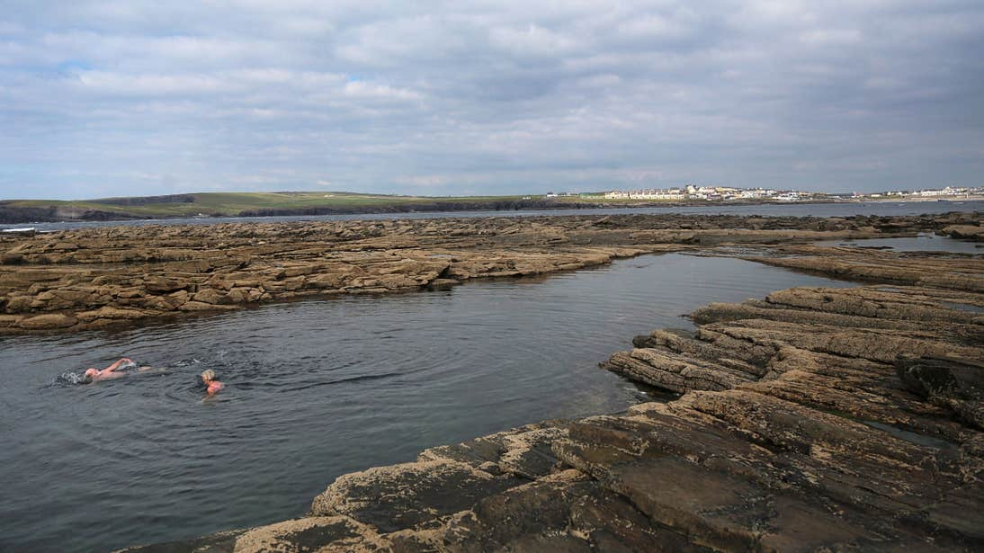 Two people swimming at The Pollock Holes in Kilkee, Clare