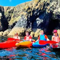 A group of six sea kayakers posing in front of caves at Newtown Cove