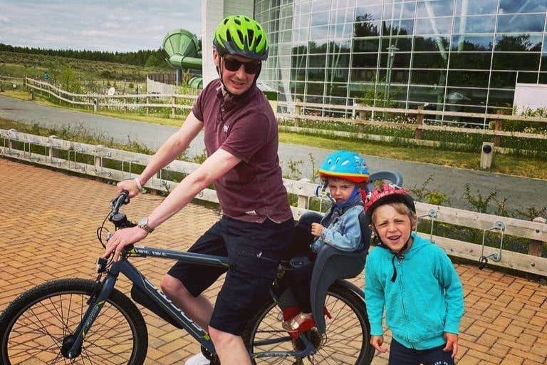 Dad and two kids off on a cycle in Centre Parcs, Longford