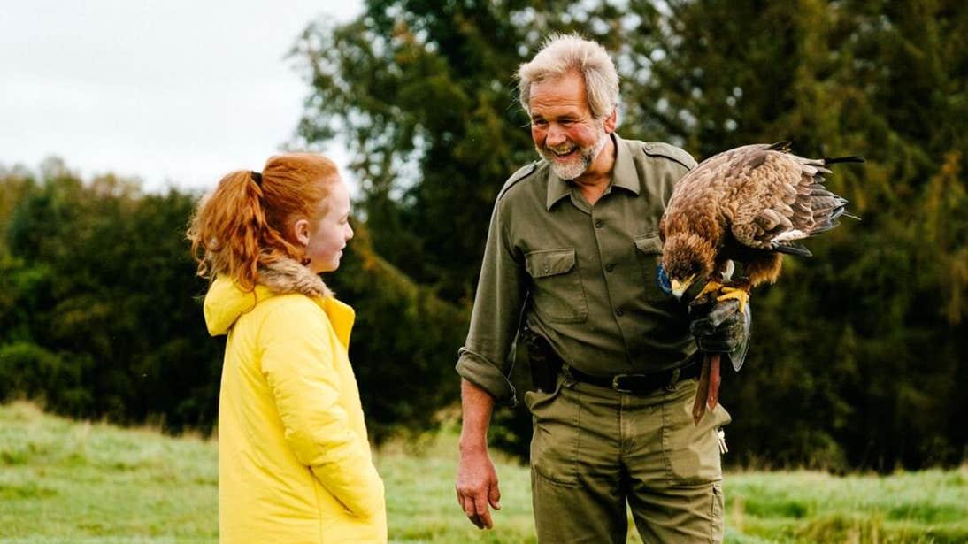A man showing a girl a bird at Eagles Flying, County Sligo