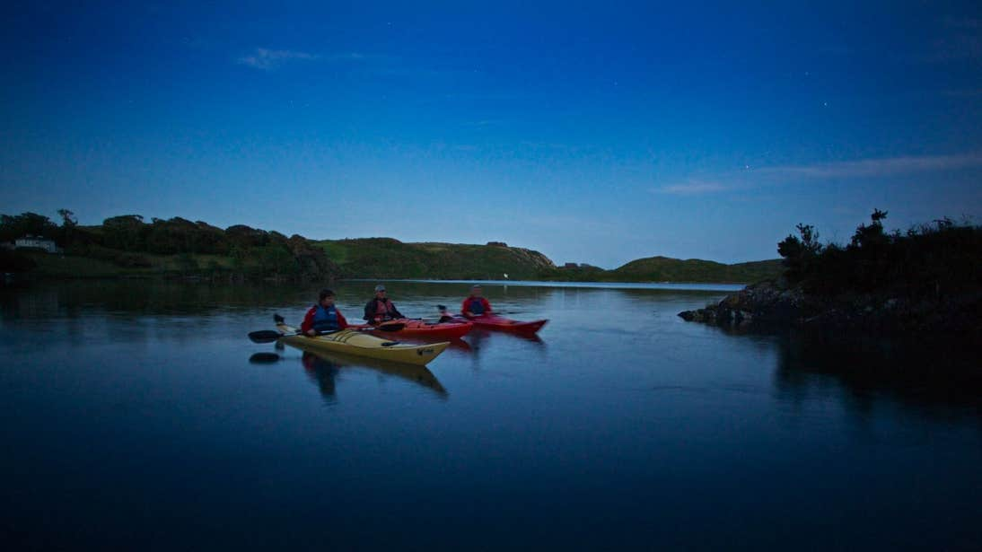 A group of people night kayaking on Lough Hyne in West Cork