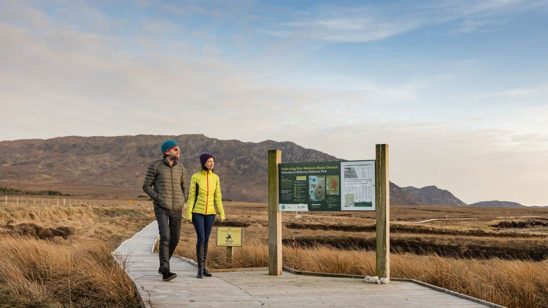 A couple walking on a boardwalk towards a sign in Wild Nephin Ballycroy, Co. Mayo