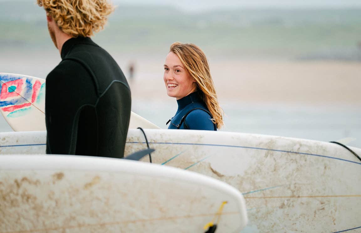 Surfers carrying surfboards at Lahinch, County Clare