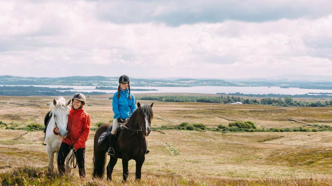 A child and an adult on a horse riding expedition with beautiful sea and mountain views