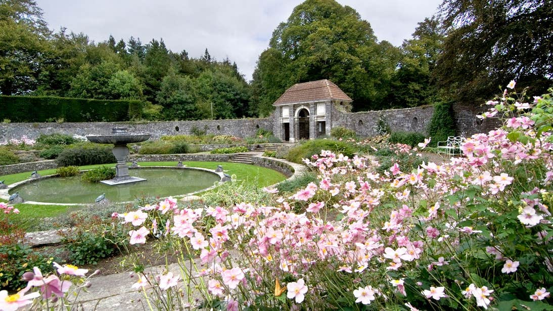 Fountain at Heywood Gardens in County Laois surrounded by a stone wall and pink flowers.