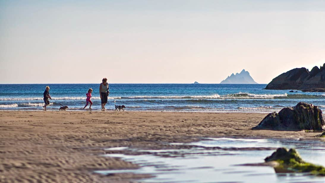 A family and dog walking on Ballinskelligs Beach, Co. Kerry