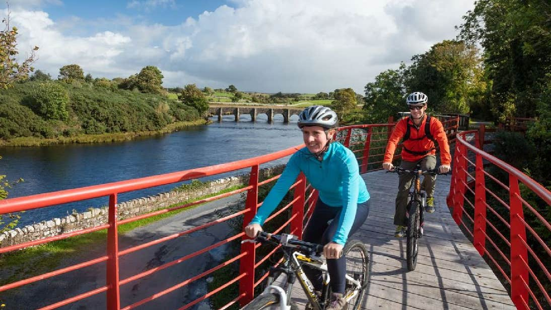 Cycle on a red bridge the Great Western Greenway in County Mayo