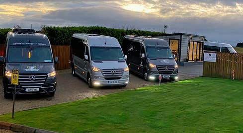 Three Mercedes class mini buses parked together at dusk with their lights on
