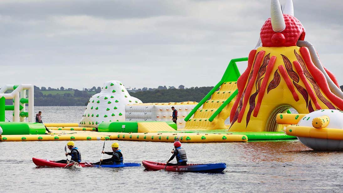 Three kayakers in the water beside inflatable toys in Athlone