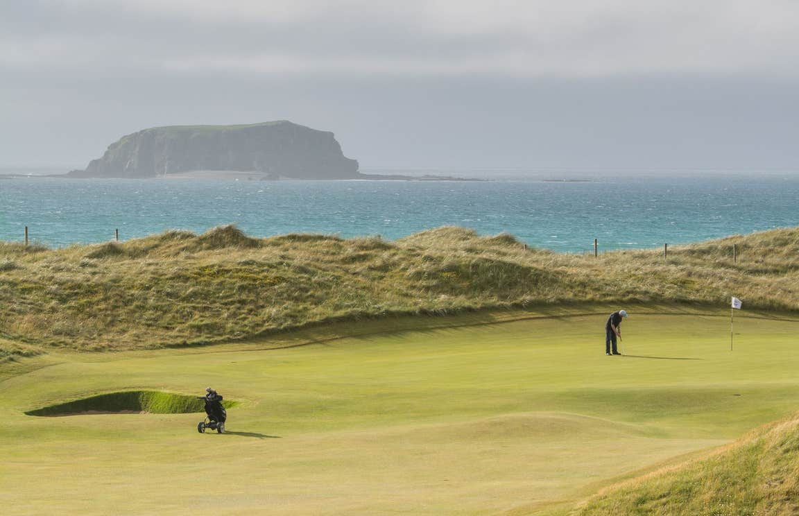 Golfer putting beside the sea at Rospaenna Golf Course, Donegal
