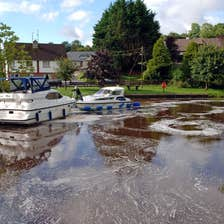 Two boats on the harbour in Ballinamore in County Leitrim near a park