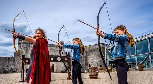 The castles resident archer with two girls all holding their bow and arrows in the courtyard