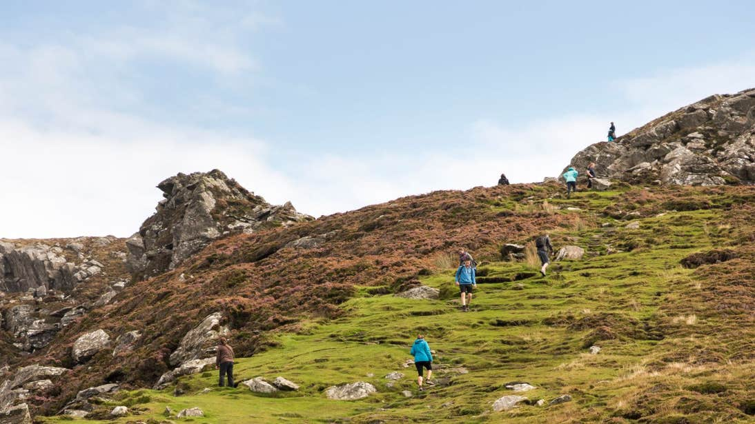 A group of people walking up a green hill at Sliabh League, Donegal