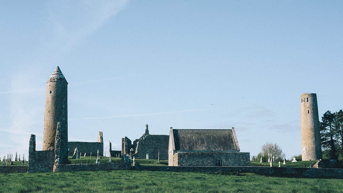 Towers and old buildings in a field at Clonmacnoise in Offaly