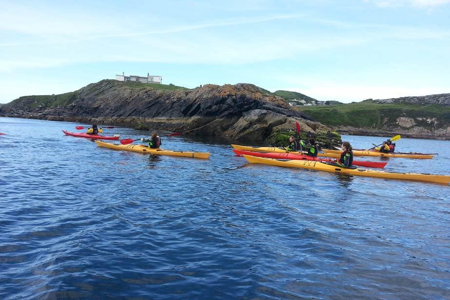 Group of kayakers paddling beside rocks in the sea.
