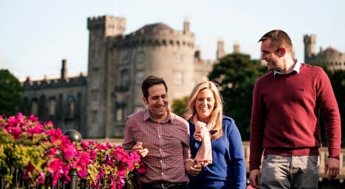 A group of friends laughing outside Kilkenny Castle beside some flowers