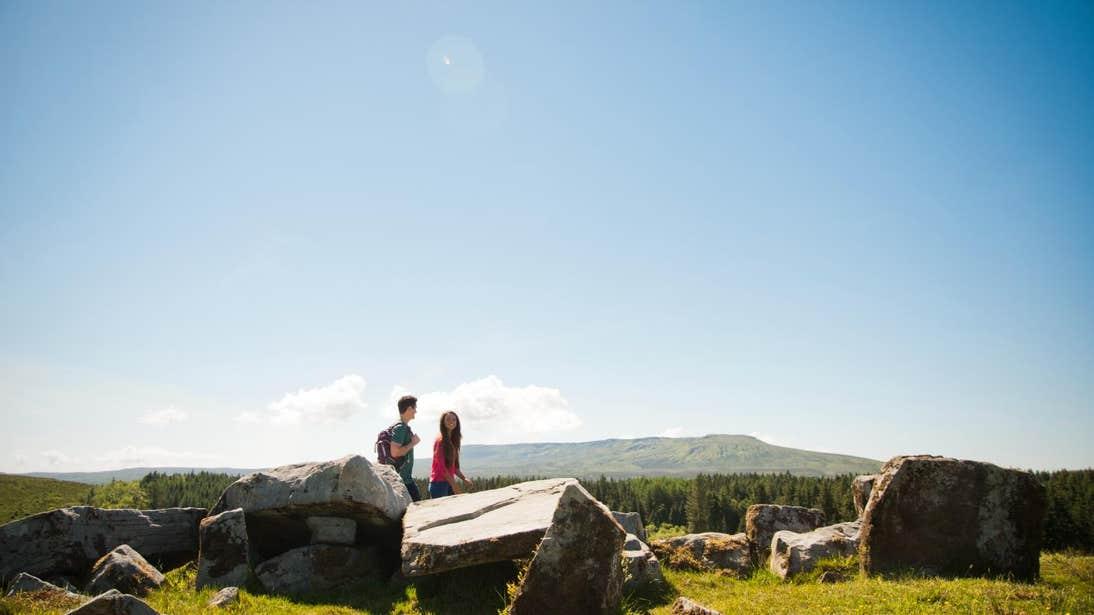 Man and woman walking through Cavan Burren Park on a sunny day