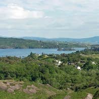 A view of Bantry Harbour in the distance surrounded by forestry taken from a vantage point within the Nature Reserve known as Lady Bantrys Lookout