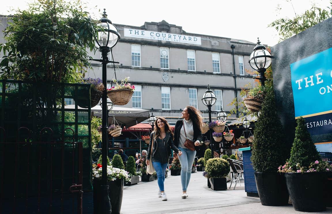 Two friends walking through a market in Cork City
