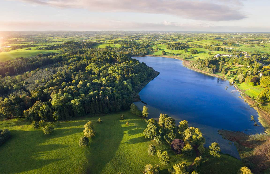 Aerial view of lush green landscapes and a clear blue lake at Castle Leslie Estate