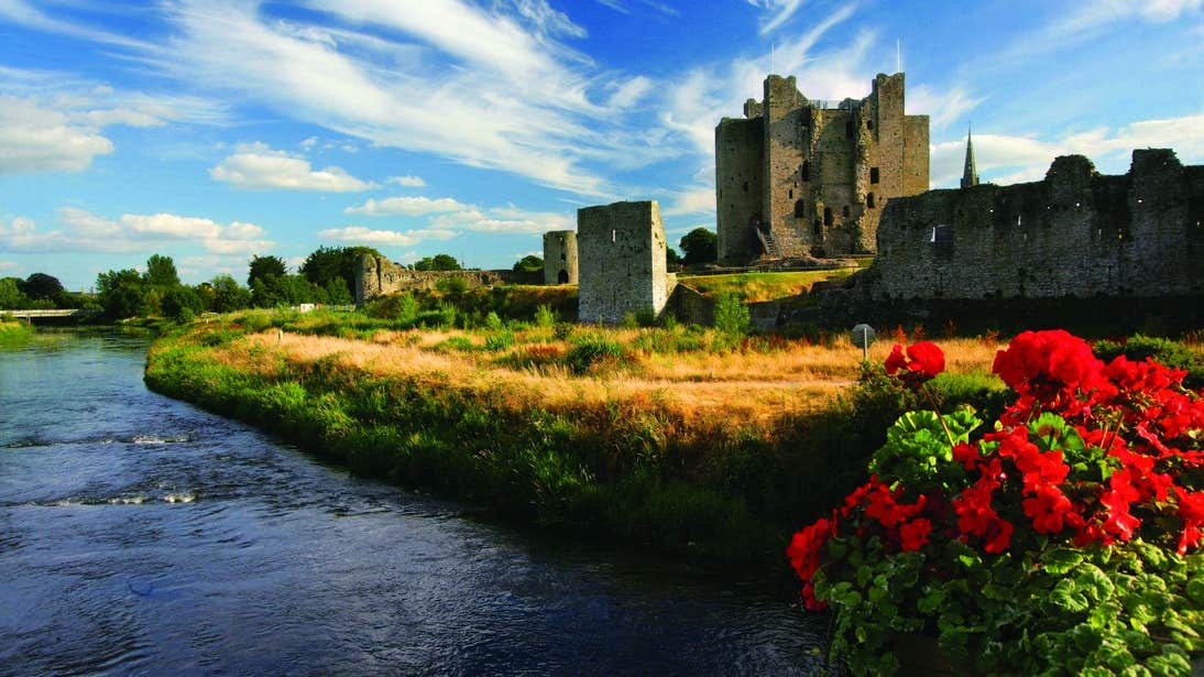 A castle beside a river with vibrant flowers and grass