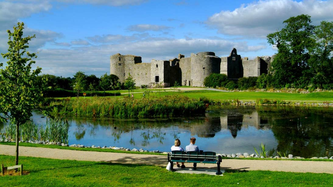 Two people sitting on a bench in front of a lake at Roscommon Castle