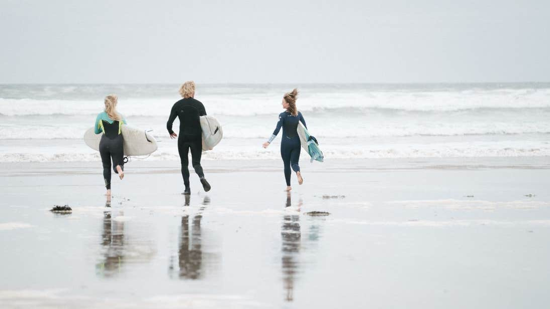 People getting into the sea to go surfing at Lahinch, Co Clare