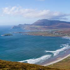 A sweeping golden beach with gentle waves at Keel Beach, Achill Island, County Mayo