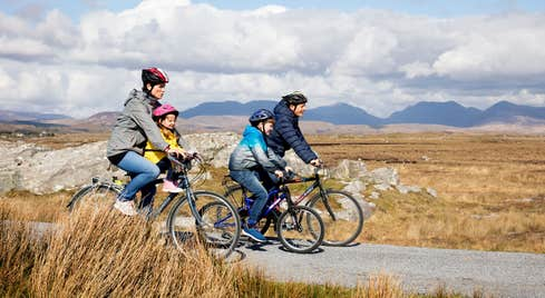 Family cycling through Derrigimlagh, County Galway