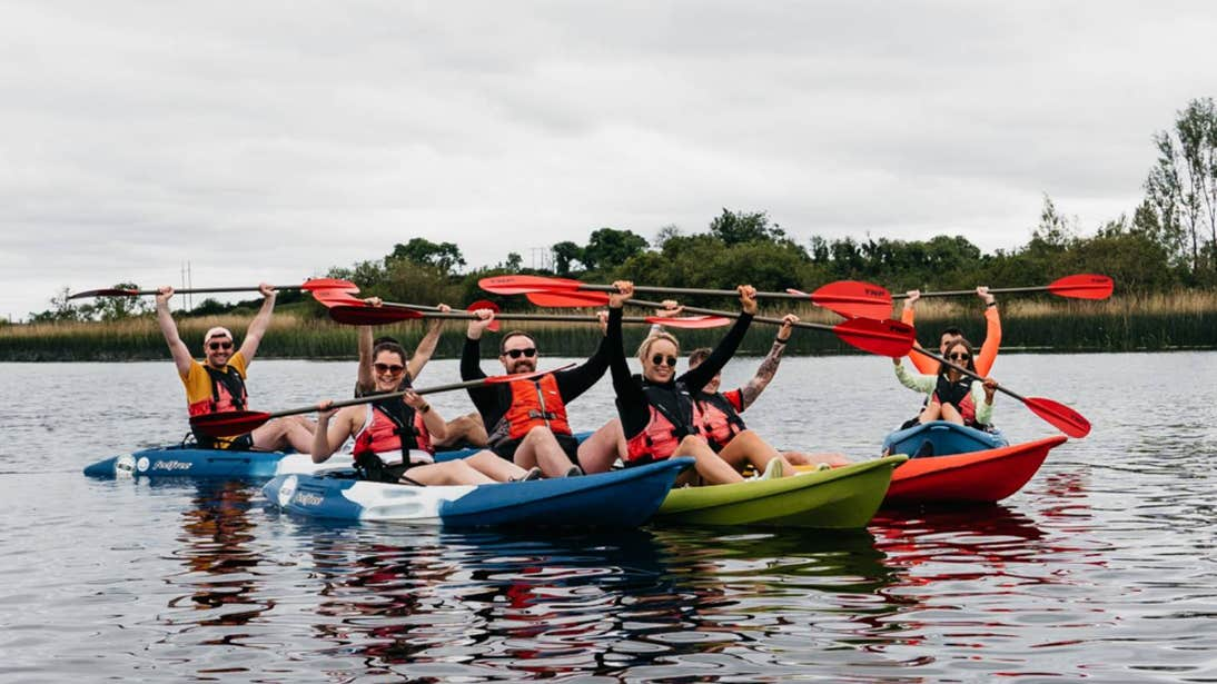 Group of people holding paddles over their heads while kayaking on the River Shannon in Leitrim.