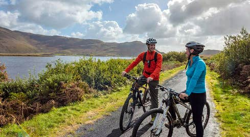 Clew Bay Bike Trail with two cyclists next to the bay and mountains